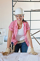 Portrait of a happy female construction worker wearing hardhat with blueprints