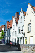 Cyclist riding past painted houses with crow-stepped gables by Groenerei (green Canal) in Bruges, Belgium