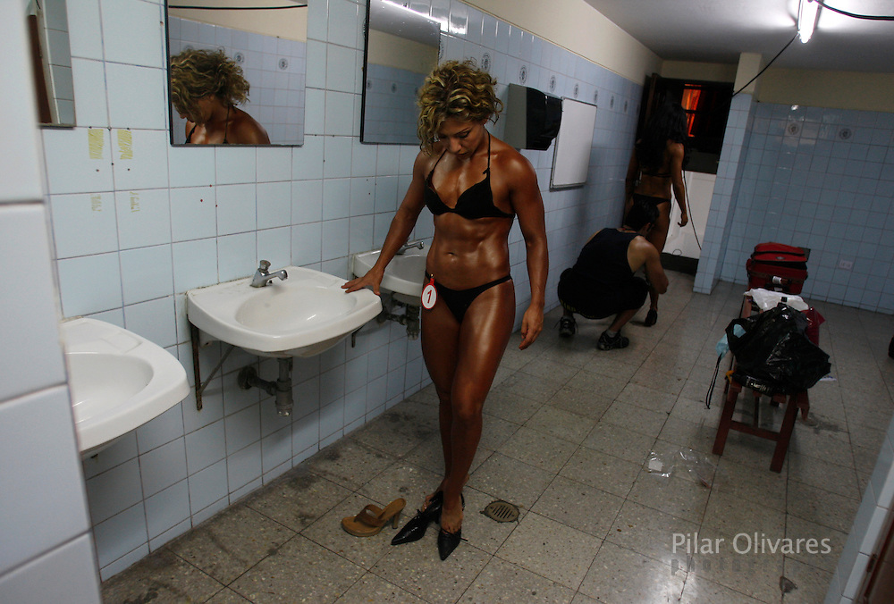 A competitor puts on her shoes before her turn in a bodybuilding competition in Lima January 30, 2010.