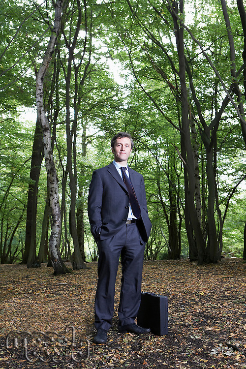 Portrait of business man in forest hands in pockets