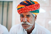 Portrait of an ethnic old Rajasthani man with mustache  belonging to the Rajput community, wearing colourful bright turban.