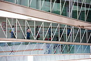 """Airline passengers make their way along jetties from their newly-arrived aircraft, towards the arrivals concourse in Heathrow Airport's Terminal 5. We see four lines of jetties that are owned by the airport operator, used by British Airways and sponsored by HSBC. Air travellers walk briskly after their long-haul flight either carrying light carry-on bags or towing small cases on wheels. At a cost of £4.3 billion, Terminal 5 has the capacity to serve around 30 million passengers a year. From writer Alain de Botton's book project """"A Week at the Airport: A Heathrow Diary"""" (2009). .."""