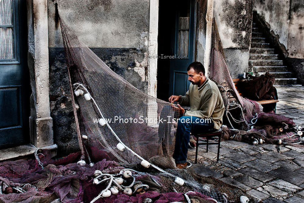 Split, Croatia, fisherman fixes his fishingnets