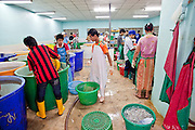 Oct. 6, 2009 -- SAMUT SAKHON, THAILAND: Burmese workers in a Thai owned shrimp processing plant sort and grade shrimp in Samut Sakhon, Thailand, Oct. 6. The Thai fishing industry is heavily reliant on Burmese and Cambodian migrants. Burmese migrants crew many of the fishing boats that sail out of Samut Sakhon and staff many of the fish processing plants in Samut Sakhon, about 45 miles south of Bangkok. Migrants pay as much $700 (US) each to be smuggled from the Burmese border to Samut Sakhon for jobs that pay less than $5.00 (US) per day.   Photo by Jack Kurtz / ZUMA Press