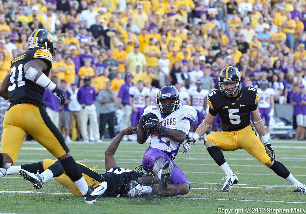 September 15 2012: Northern Iowa Panthers wide receiver Terrell Sinkfield (2) is brought down by Iowa Hawkeyes defensive back B.J. Lowery (19) as linebacker Anthony Hitchens (31) and defensive back Tanner Miller (5) look on during the second half of the NCAA football game between the Northern Iowa Panthers and the Iowa Hawkeyes at Kinnick Stadium in Iowa City, Iowa on Saturday September 15, 2012. Iowa defeated Northern Iowa 27-16.