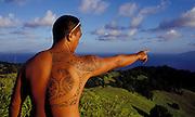 Tätowierter Mann deutet auf die Küste und den Südpazifik, Hiva Oa, Französisch Polynesien *  Tatooed man, pointing at coast and South Pacific, Hiva Oa, French Polynesia