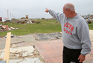 Ed Thomas, of Parkersburg, a teacher and football coach at Aplington-Parkersburg High School points from the site where his house once stood and explains the path of the tornado in Parkersburg, Iowa on Wednesday June 4, 2008. (Stephen Mally for the New York Times)