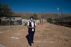 Abrey Arendse, Operational Manager at De Doorns Clinic, a Western Cape government facility, stands outside the fenced clinic premises, where the staff has painted social-distancing lines on the ground, Wednesday May 6, 2020. Each morning, hundreds of patients line up here, says Arendse. And, she, herself, greets everyone to see who needs to come inside the clinic right away, including the elderly, very sick, pregnant ladies and disabled people. The COVID-19 pandemic is a challenge, she says. There is not enough PPE on hand for patients and no long-term stock for staff. It's also difficult to leave patients waiting outside. The sun is strong, and the winter rains are coming. De Doorns is a town in the Breede Valley Local Municipality, Cape Winelands District Municipality, in the Western Cape province of South Africa. PHOTO: EVA-LOTTA JANSSON