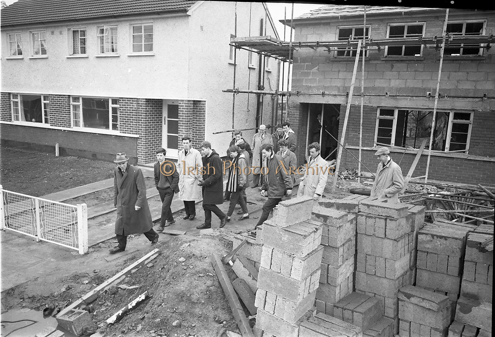 "01/04/1963<br /> 04/01/1963<br /> 01 April 1963<br /> Students from Bolton Street College of Technology visit ""Greenfield"" (Wates) Housing Estate at Ballymun, Dublin.  Mr George Madden, storekeeper at Wates Greenfield Estate and Mr. William Gilligan, B.A., M.R.I.A.I., showing a group of students around the estate."