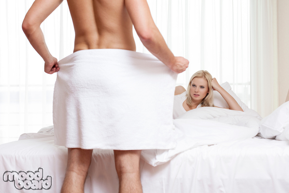 Young woman staring at naked man holding towel in bedroom