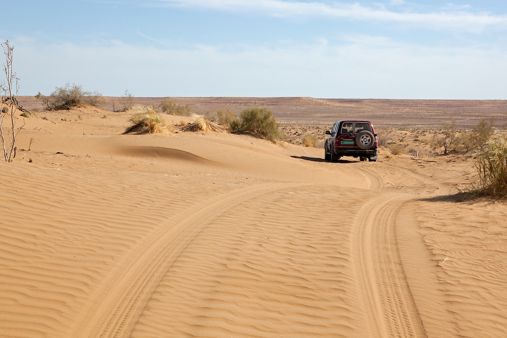 A Land Cruiser traverses the sand dunes of the mostly scrubland desert, the Karakum, that covers most of Turkmenistan