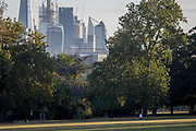 With the skyline of the capital's financial district, the City of London in the distance, a woman does lunges in Ruskin Park, on 10th August 2018, in London, England.