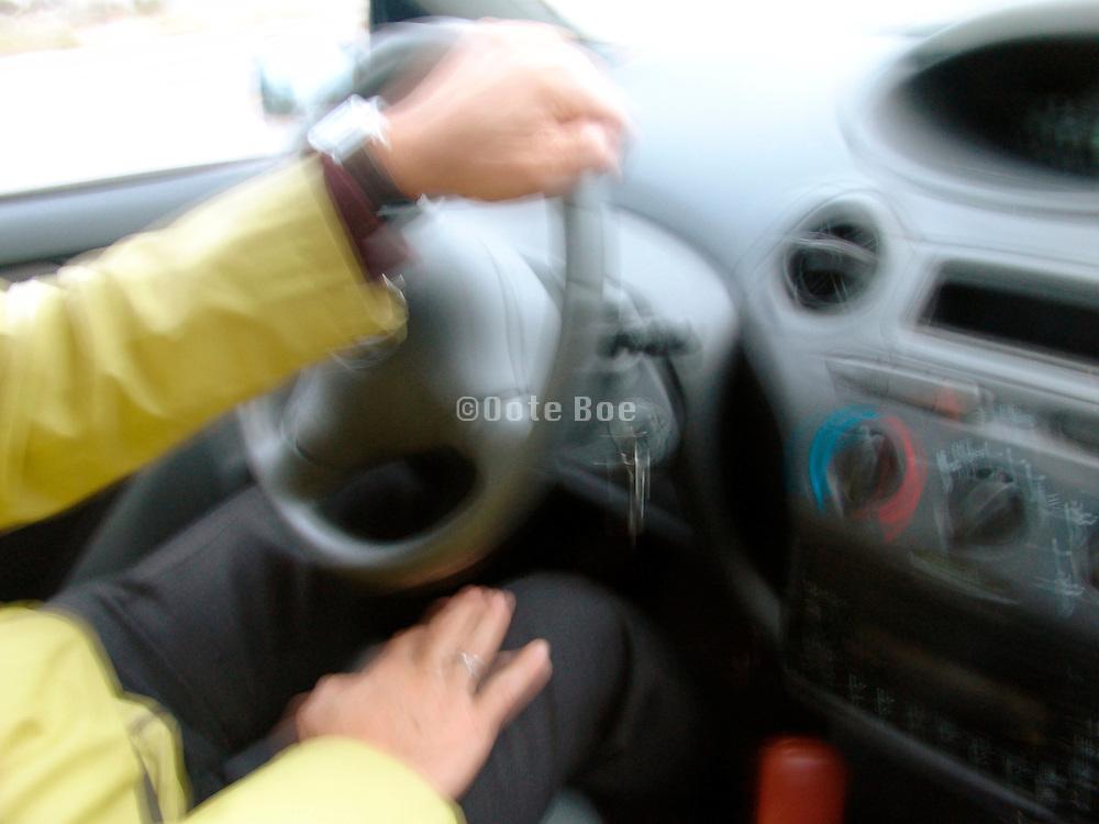 Hand turning a steering wheel.