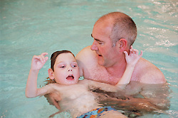 Father supporting young son with severe Cerebral Palsy; cortical blindness; epilepsy and severe developmental delay in public swimming pool,