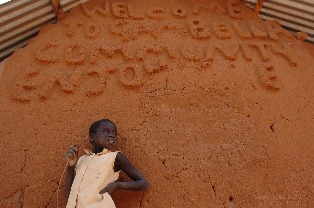 A young girl, from the Gambella region of Ethiopia, stands near a sign welcoming visitors to her community at Ifo Refugee Camp in Dadaab, Kenya September 15, 2006. ..Photograph by Erin Lubin