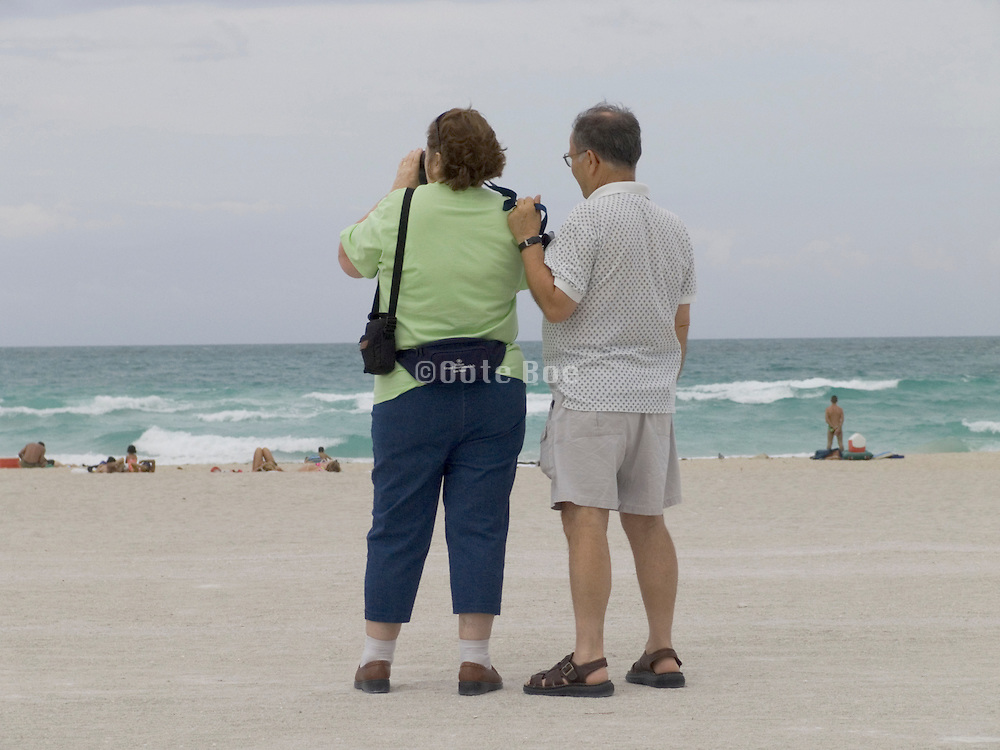 couple watching people laying on the beach Miami USA