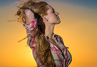 Young caucasian woman relaxing at sunset with hair free to the wind.
