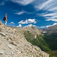 summer hiker in glacier park admires wispy, magical clouds blue sky