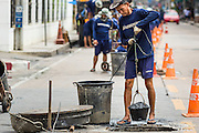 24 AUGUST 2013 - BANGKOK, THAILAND:      A prisoner pulls a bucket of sewage out of a sewer in Bangkok. A work gang from a prison near Bangkok was cleaning the sewers along Soi 22 Sukhumvit.   PHOTO BY JACK KURTZ