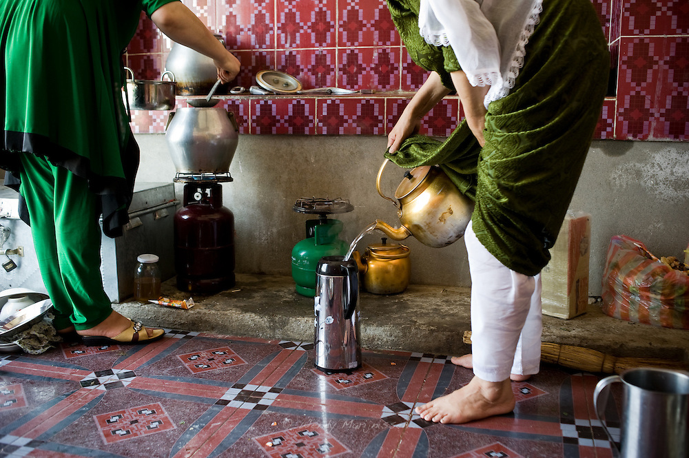 Two women cook and make tea. Women are still soley responsible for running the household and raising children in Afghan society. Faizabad, Badakshan, Afghanistan, 2012