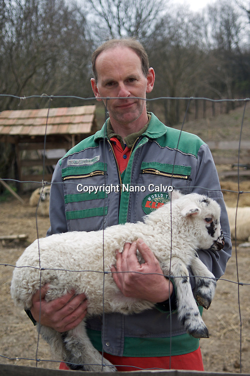 Rancher holding lamb for tourists to see and touch. <br /> <br /> Traditional costumes and folk traditions at Easter Festival in Holl&oacute;kő, UNESCO World Heritage-listed village in the Cserh&aacute;t Hills of the Northern Uplands, Hungary.