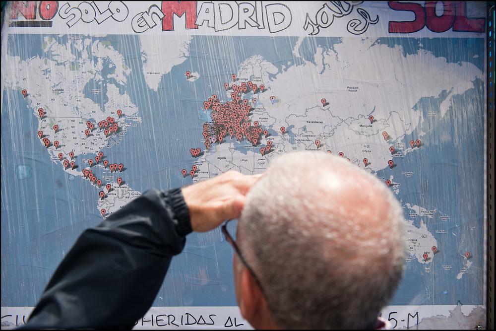"""Une carte du monde representant les villes ou le mouvement du 15 M est repri est affichee dans le camp place Puerta Del Sol. // Le mouvement spontane du """"15 M"""" (15 mai) compose de citoyens espagnols campe depuis 2 semaines sur la place Puerta Del Sol avec pour revendication la construction d'une democratie nouvelle. Organise en commission les citoyens prennent la parole lors d'assemblee ouverte a tous - Place Puerta Del Sol à Madrid le Juin 2011. ©Benjamin Girette/IP3Press"""