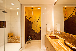 Master bathroom with orange motif of marble and tile. Interior designed by Andee Hess of Osmose.