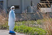 A Japanese couple in makeshift radiation suits visit their house for the last time in the town of Tomioka, Futaba District of Fukushima, Japan. Thursday May 2nd 2013. The town was evacuated on March 12th after the March 11th 2011 earthquake and tsunami cause meltdowns at the nearby Fukushima Daichi nuclear power station. It lies well within the 20 kms exclusion zone though parts of the town were opened again in spring 2013 to allow locals to visit their property during daylight hours.