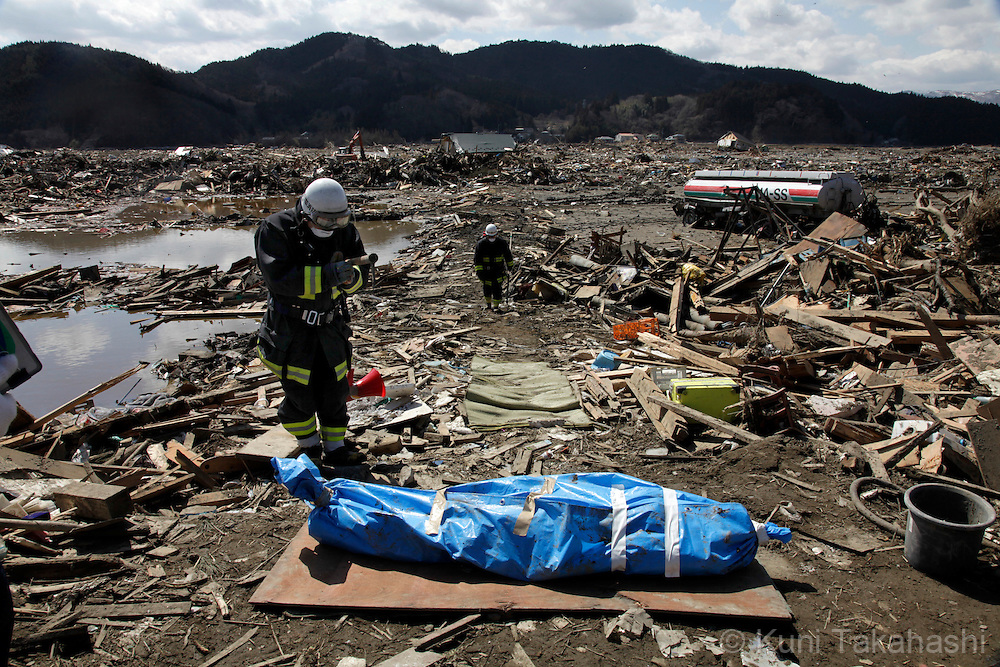 A firefighter prays in front of a body of a victim in Rikuzentakata in Iwate, Japan after massive earthquake and tsunami hit northern Japan. More than 20,000 were killed by the disaster on March 11.<br /> Photo by Kuni Takahashi