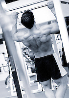 Young man doing chin-ups on bar in gym, rear view (B&W)