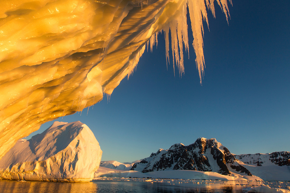 Antarctica, Setting midnight sun lights icicles hanging from melting iceberg at southern end of Lemaire Channel near Petermann Island