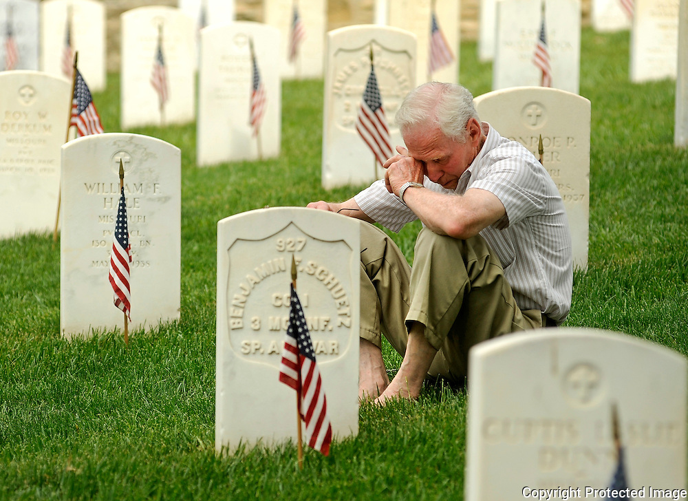 Kris Wilson/News Tribune<br /> Gene Wilson of Jefferson City wipes his eyes as he sits among the marble headstones of some of Missouri's military dead while listening to retired Army Major General Henry Stratman speak of the costs of war during Monday's Memorial Day program at the Jefferson City National Cemetery.