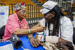 Sadie Reaves, left, takes the blood pressure of Dale Pringle.  Project Homeless Connect  connects those in need of support with vital resources and services.  St. Thomas, USVI.  4 December 2015.  © Aisha-Zakiya Boyd