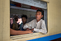 YANGON, MYANMAR - CIRCA DECEMBER 2013: Burmese man looking away from a train window while it waits for departure in Yangon Central Railway Station