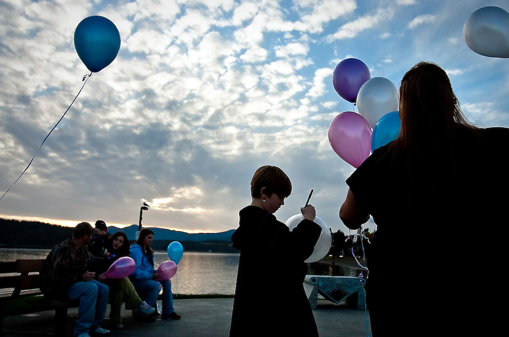 JEROME A. POLLOS/Press..Miranda Brown, 10, writes a message on a balloon Thursday for her baby sister Rachel who died. Brown's mother, Jennifer Brown, helped organize the event at Independence Point for Pregnancy and Infant Loss Remembrance Day.
