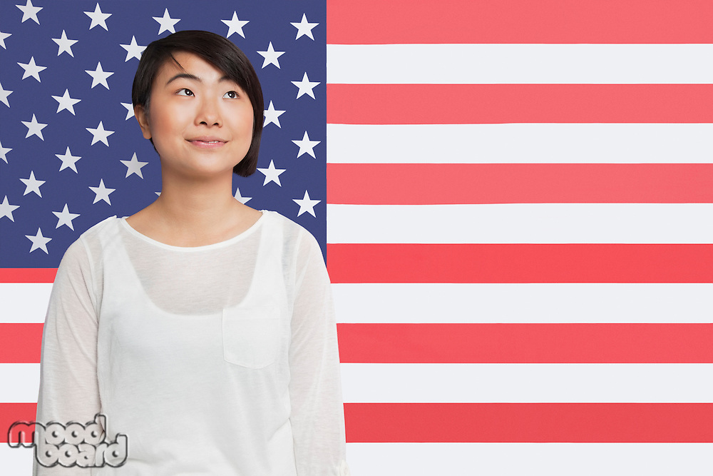 Thoughtful Asian woman looking away against American flag