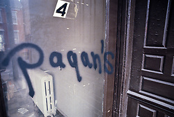 graffiti pagans sign on apartment door window.  Pagan's are notorious regional motorcycle gang.