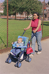 Young mother pushing baby son in pushchair along pavement next to park,