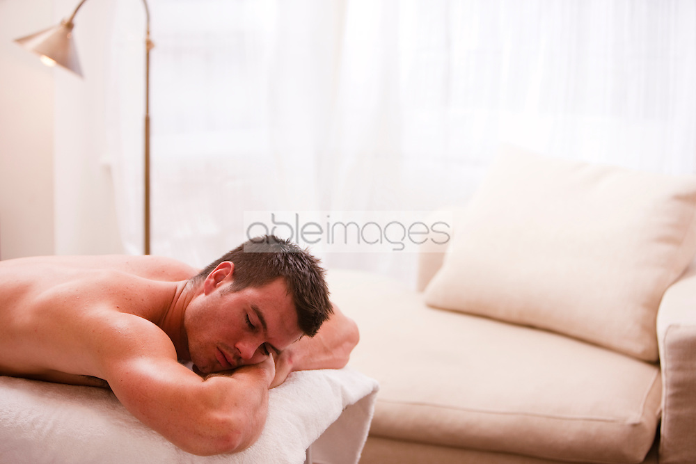 Man lying on his stomach on a treatment bench
