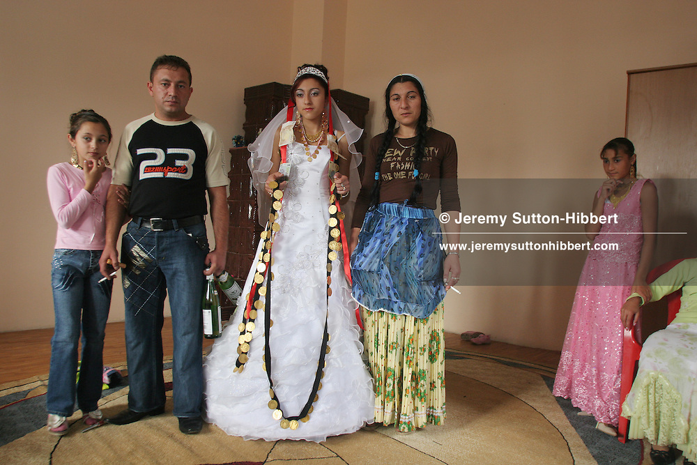 Fourteen year old Garoafa Mihai stands with her mother Papusha, father Grafian and sister Isabella, on her wedding day in the village of Sintesti, Romania, on Sunday, Sept. 24th 2006. Day two of the wedding between Garoafa Mihai, aged 14, and Florin 'Ciprian' Lulu, aged 13, Roma (gypsies) from the village of Sintesti,15 kilometres from Bucharest, Romania. Their partnership was decided by their parents and not through love, and under Romanian law is illegal. The children will neither complete legal paperwork for the wedding, nor visit the local Romanian Orthodox church for a blessing. On her wedding day Garoafa wore approximately 30-40,000 USD of gold Franz Josef coins on her dress, part of the large dowry that she takes with her as she begins her married life. For the guests and for the people of the village another 30,000 USD of pigs, approximately 100,  were killed to be eaten and given away as presents of food. Another 30,000 USD was spent on famous Roma musicians to come and sing 'manele'  type music at the wedding extolling the wealth and status of their patrons for the weekend in their songs.