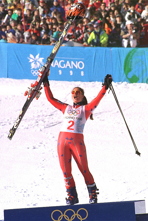 Picabo Street of the USA kneels for a moment on the podium after winning a gold medal in the Womens Super G at the Nagano Winter Olympics in February 1998. Photo by August Miller