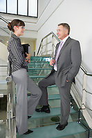 Business man and woman talking on stairs in office building