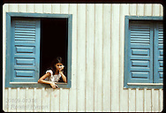 Girl stares out window of wooden home in town of Eirunepe, state of Amazonas. Brazil
