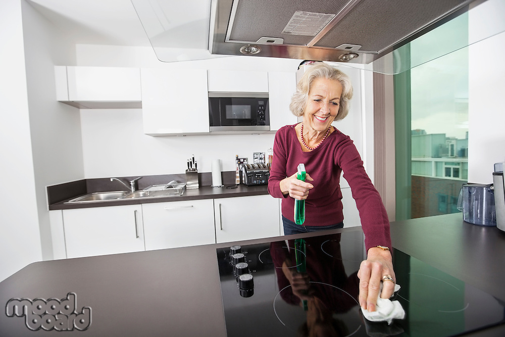 Happy senior woman cleaning kitchen counter