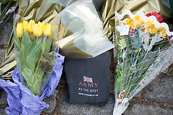 © London News Pictures. 23/05/2013. Woolwhich, UK. Flowers and a military t-shirt t-shirt left outside Woolwich Barracks in Woolwhich, London where a member of the armed forces was attacked yesterday (22/05/2013) by two men in what is being described as a terrorist attack. Photo credit: Ben Cawthra