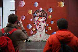 © Licensed to London News Pictures. 11/01/2016. London, UK. People gather at a mural to David Bowie in Brixton. The Death of David Bowie has been announced. Photo credit: Peter Macdiarmid/LNP
