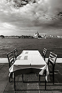 A table with chairs of a restaurant on the watefront sidewalk of the Giudecca island in Venice, Italy