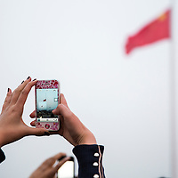 China, Beijing, Young woman holds cellphone camera aloft to take snapshots of lowering of Chinese flag in Tiananmen Square on fall evening