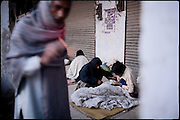 """Homeless heroin users slowly wake up early in the morning. Two of them are negotiating a dose of drug. Rawalpindi, Pakistan, on thursday, November 27 2008.....""""Pakistan is one of the countries hardest hits by the narcotics abuse into the world, during the last years it is facing a dramatic crisis as it regards the heroin consumption. The Unodc (United Nations Office on Drugs and Crime) has reported a conspicuous decline in heroin production in Southeast Asia, while damage to a big expansion in Southwest Asia. Pakistan falls under the Golden Crescent, which is one of the two major illicit opium producing centres in Asia, situated in the mountain area at the borderline between Iran, Afghanistan and Pakistan itself. .During the last 20 years drug trafficking is flourishing in the Country. It is the key transit point for Afghan drugs, including heroin, opium, morphine, and hashish, bound for Western countries, the Arab states of the Persian Gulf and Africa..Hashish and heroin seem to be the preferred drugs prevalence among males in the age bracket of 15-45 years, women comprise only 3%. More then 5% of whole country's population (constituted by around 170 milion individuals),  are regular heroin users, this abuse is conspicuous as more of an urban phenomenon. The substance is usually smoked or the smoke is inhaled, while small number of injection cases have begun to emerge in some few areas..Statistics say, drug addicts have six years of education. Heroin has been identified as the drug predominantly responsible for creating unrest in the society."""""""