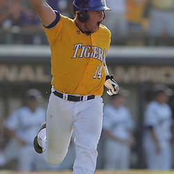 Sean Ochinko #14 of LSU pumps his fist in the air as he runs, to first base, his hit knocked in the go-ahead run in the top of the ninth inning. The LSU Tigers defeated the UC Irvine Anteaters 9-7 with a ninth inning rally in game two of a three game NCAA Baseball Super Regional playoff at Alex Box Stadium in Baton Rouge, LA..
